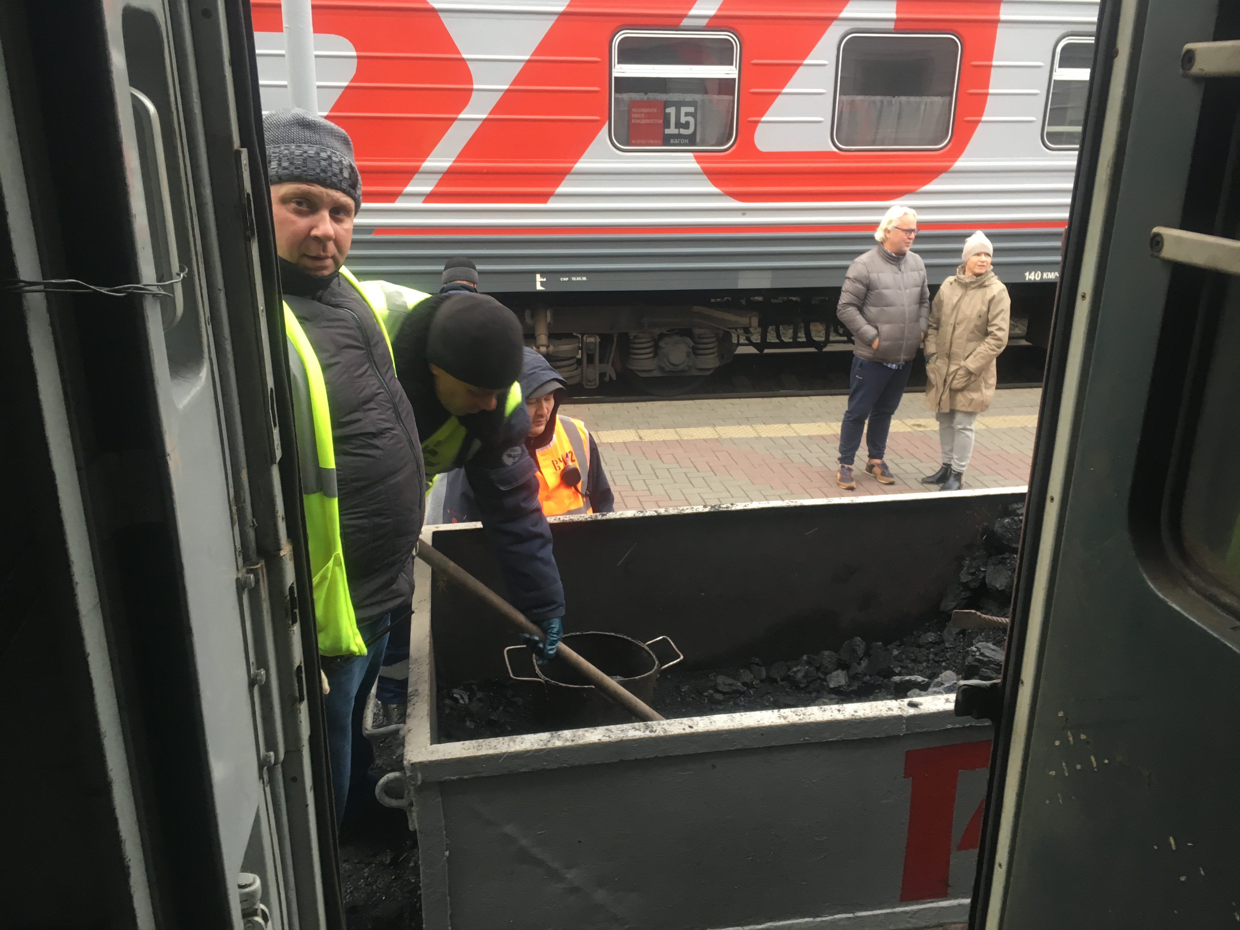 Sauli and Maria watching the coal delivery at Omsk (and the coal man watching me