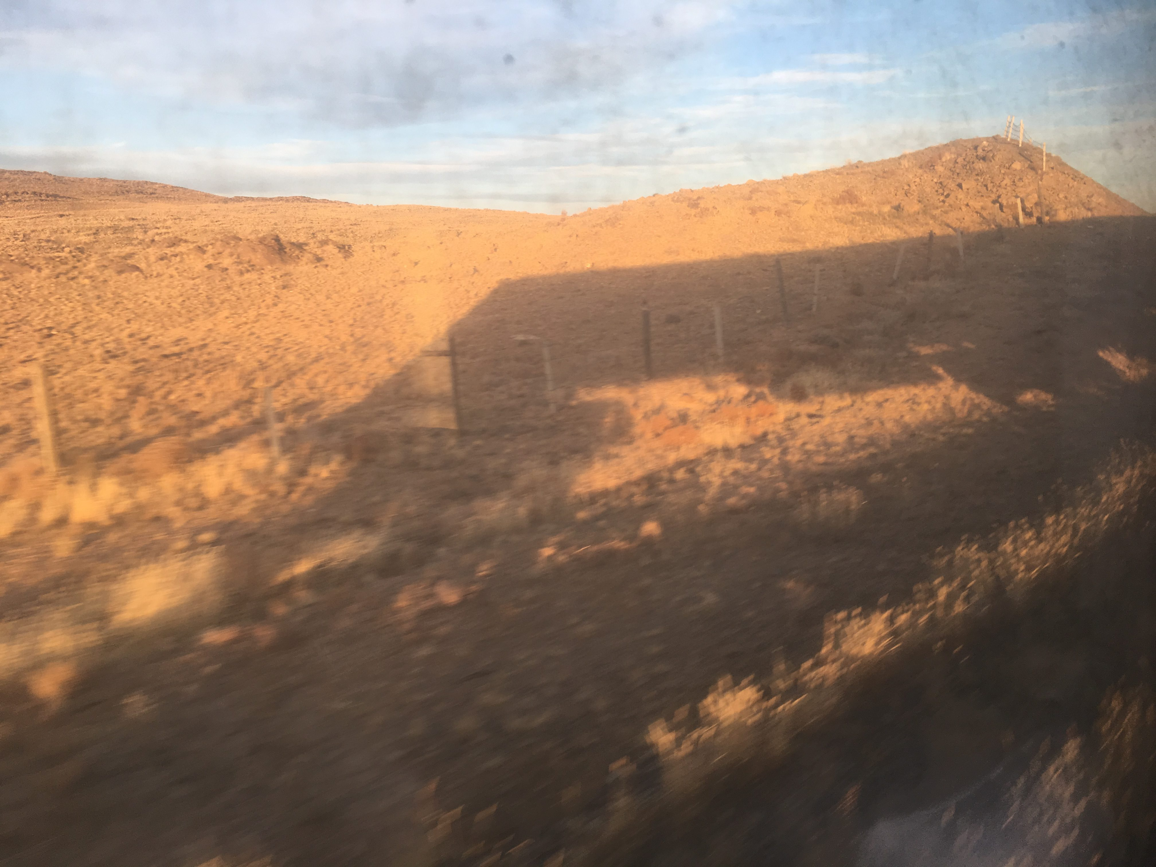The shadow of our train crests the Mongolian hill