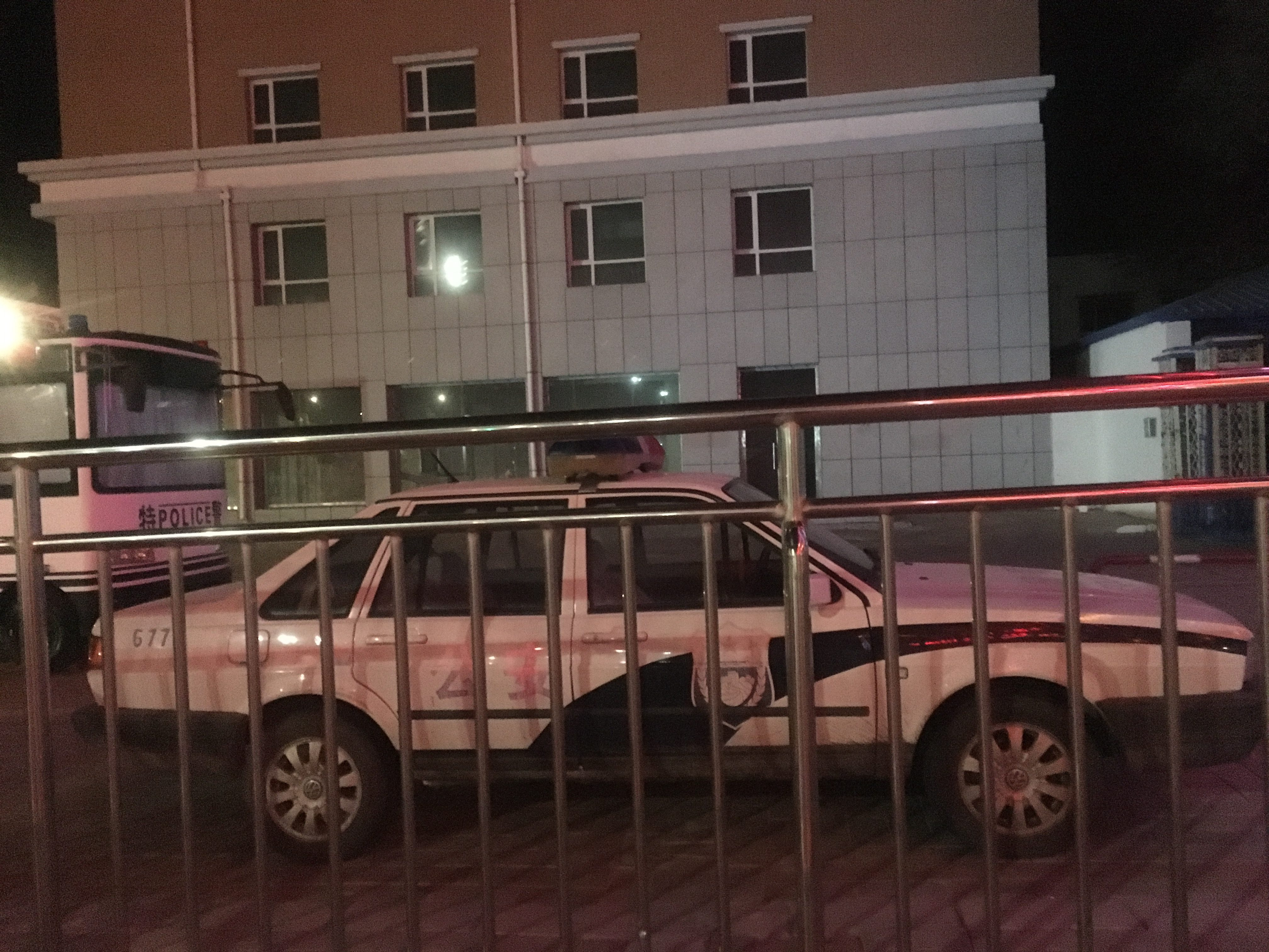 Official Chinese vehicle seen through bars of holding pen