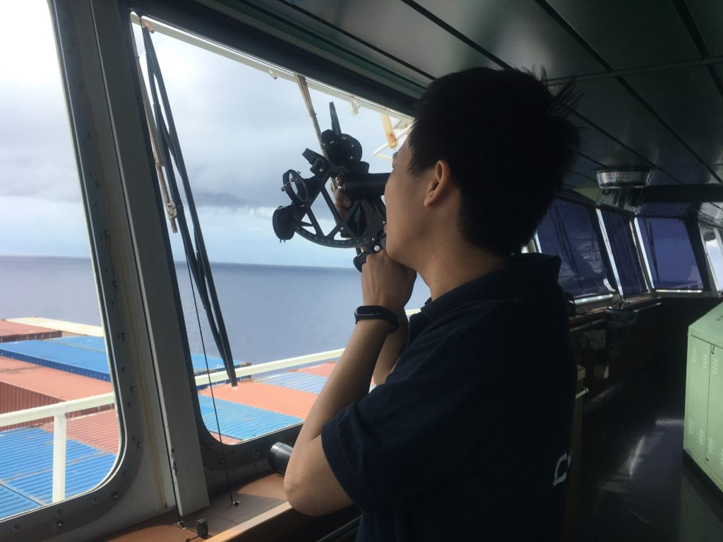 Third Officer demonstrates the sextant, taking a reading from the horizon